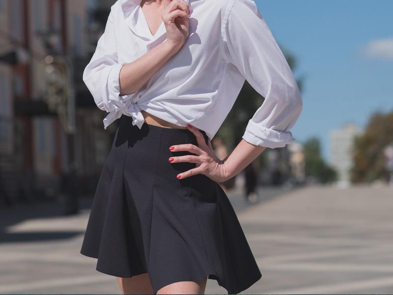 Das Foto zeigt eine Frau im Minirock und geknoteter Bluse. Ist das ein Business-Outfit für heiße Tage.